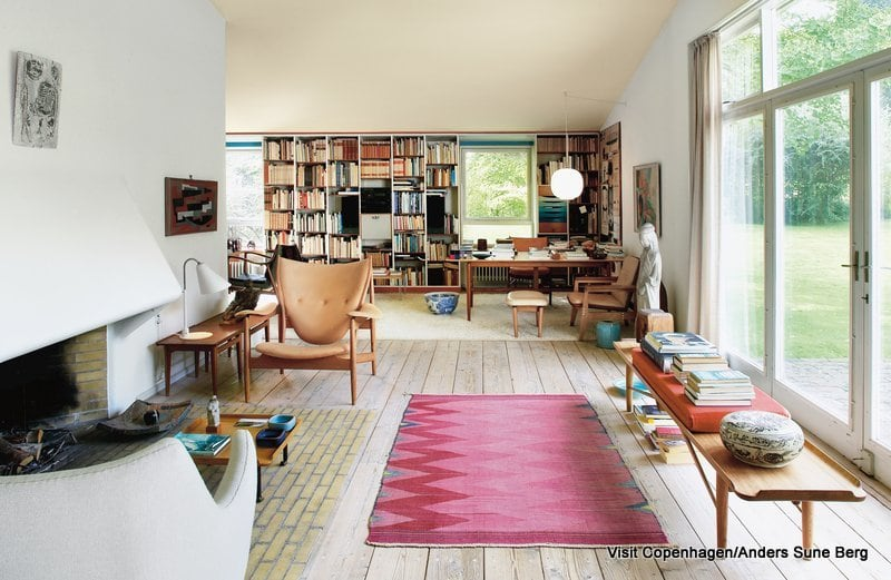 Finn Juhl's own house is a textbook example of his project as an architect and as a furniture designer. The house at Kratvænget 15 in Charlottenlund, north of Copenhagen was built in 1942. It is situated in rural surroundings on a 1700 m² site adjoining the park at Ordrupgaard.   The house is composed of two blocks standing at right-angles to each other. In one block is a large living room and a small study, while the second block houses the kitchen, dining room, bedrooms and bathroom. The two blocks are joined by an entrance hall which opens to the garden. The house is an early example of open-plan, with a characteristic view through its rooms. Although each room has its own clear function, it is always possible to look from one room to the next as you walk through the house and there is always a view of the garden. The ceilings are painted in pale light yellow and when they reflect the light from outside, they resemble the roof of a tent with light shining through. The house is brick-built and the façade is plastered in a grey-white shade which offers it a soft, matt effect. Therefore the house appears light against the contrasting dark woodland backdrop.